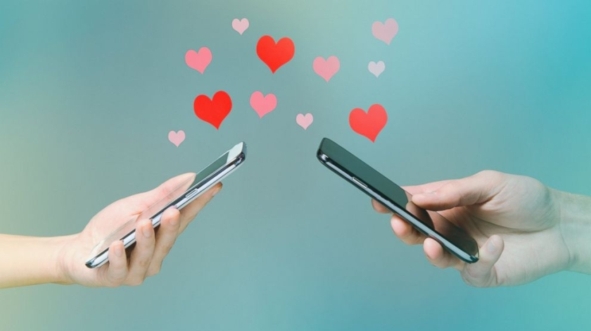 Boy and Girls hands each holding a phone. Texting one another with pink and red hearts floating up from the phones.