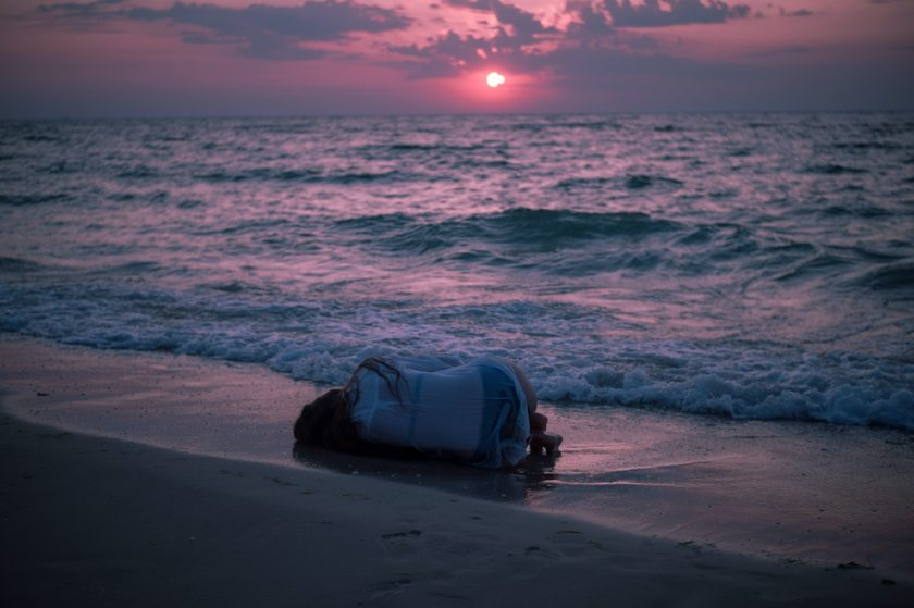 photo of person lying down on beach as the sun set in pinks and blues
