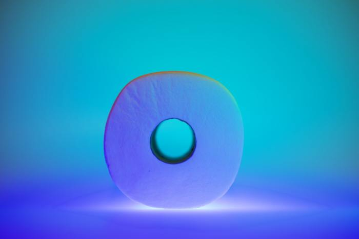 one roll of toilet paper in a blue-green and purple room